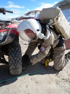 Darrel repairing Opportunity's left front tire